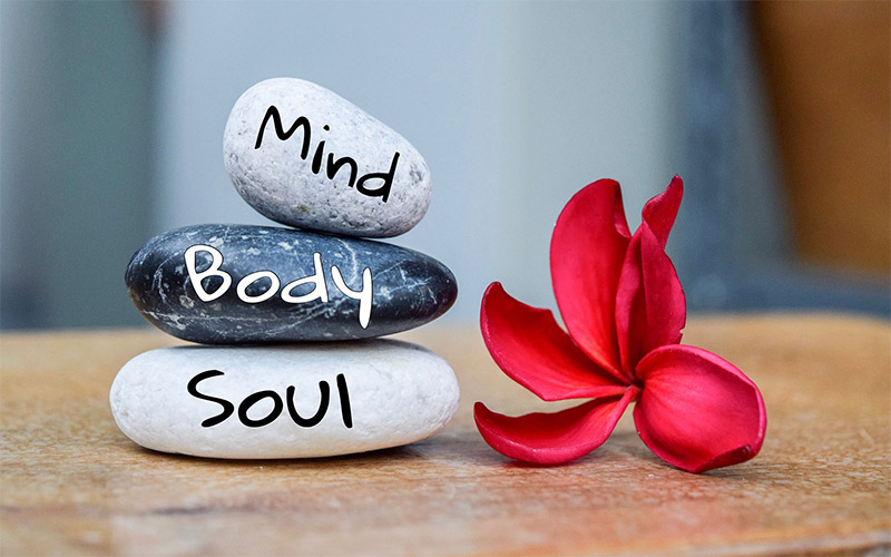 Holistic health concept of zen stones. Text with body mind soul